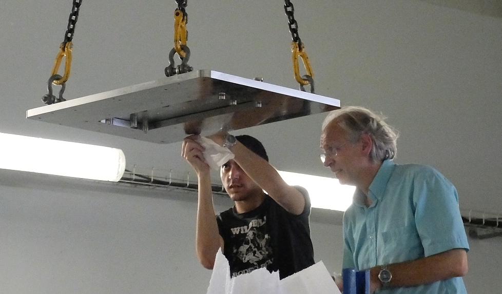 photo of two people cleaning a large suspended rectangular flange