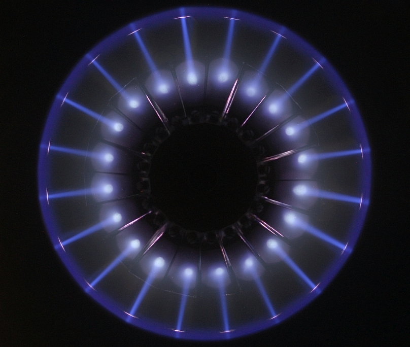 Photo of 20 argon ion beams creating 20 sputter spots on 20 individual targets on a central target block, typical for multi beam sputter deposition on circular substrates